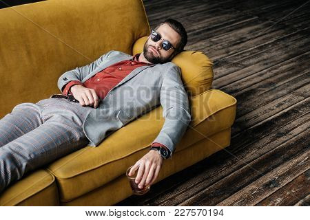 Stylish Drunk Man In Sunglasses Holding Glass Of Whiskey And Lying On Yellow Sofa