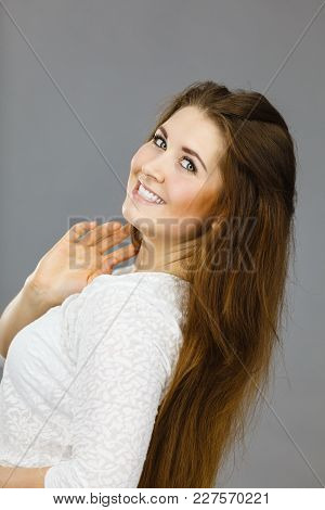 Happy Positive Woman With Long Brown Hair Presenting Her Healthy Hairdo. Haircare Concept. Studio Sh