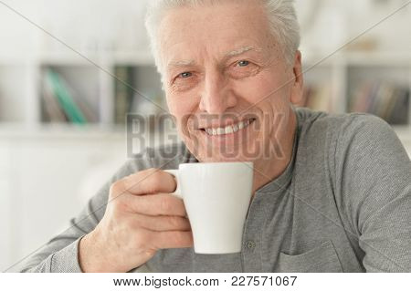 Portrait Of Smiling Senior Man Drinking Tea At Home