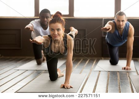 Group Of Sporty Young Afro American And Caucasian People Practicing Yoga Lesson With Smiling Instruc
