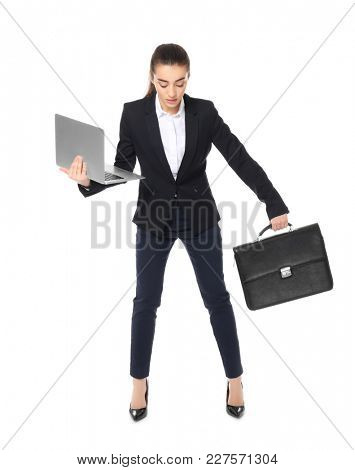 Young businesswoman with laptop and briefcase balancing on white background