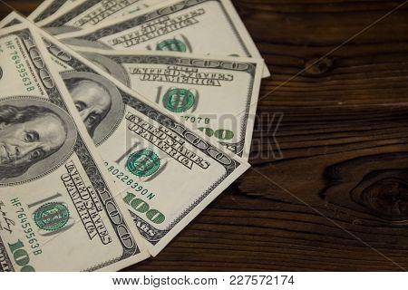 One Hundred Dollars Bills On Wooden Desk