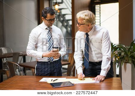 Young And Senior Coworkers In Ties And White Shirts Reviewing Documents On Desk. Boss Scolding Manag