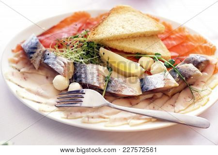 Raw Fish Plate, Tuna, Salmon And Herring With Onion Rings And Lemon On A Table Top View