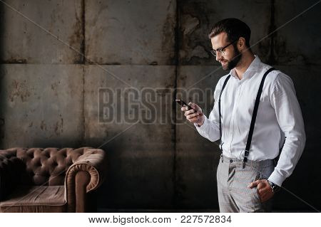 Fashionable Bearded Man In Suspenders Using Smartphone