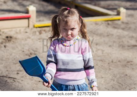 A Resent Little Girl Is Standing In A Sandbox Holding A Plastic Shovel