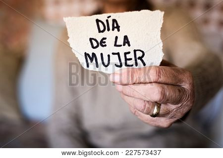 closeup of an old caucasian woman indoors showing a piece of paper with the text dia de la mujer, womens day written in spanish