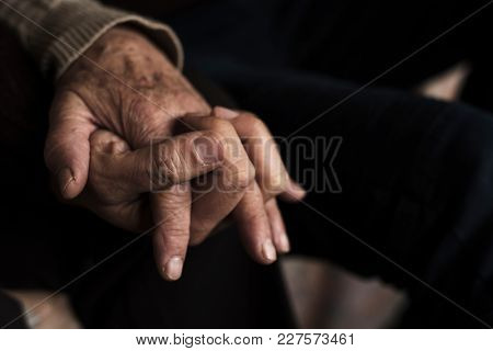 closeup of a young caucasian man holding the hand of an old caucasian woman, with their fingers entwined with affection