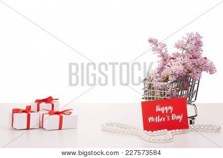Shopping trolley with brenches of Lilac, pearl beads and gift boxes  on white background. Copy space for adding your content.  Advertising. Greeting card. Mothers day.