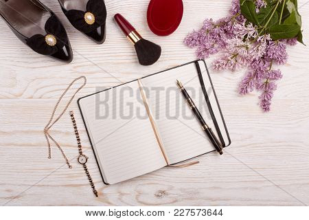 Trendy woman's desk with blank notepad for text, shoes, gifts, jewelry,cosmetics and lilac flowers on ligth wooden background. Top view. Mockup.