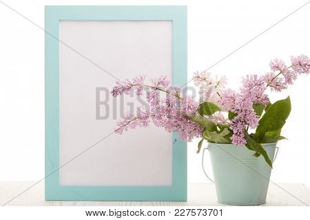 Black board with blank space for text, bouquet of  Lilac flowers in a vase on a wooden table on a white background. Copy space for adding your content.  Advertising