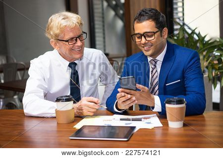 Two Colleagues Drinking Coffee, Looking At Mobile Phone Screen And Smiling. Coworkers Having Video C