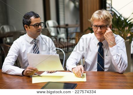 Young And Senior Men In Ties And White Shirts Sitting At Desk With Documents In Office Lobby. Two Ma