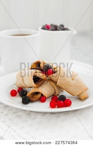 Bagels Cookies With Berries On A White Plate On A Table Next To Two White Cups
