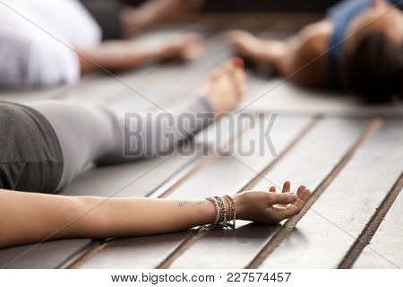 Group Of Young Sporty People Practicing Yoga, Lying In Corpse Pose, Savasana Exercise, Working Out,