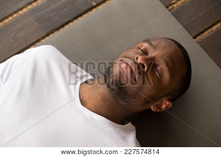 Photo Of Young Black Man Lying In Dead Body Exercise Or Corpse Pose With His Eyes Closed, Savasana P