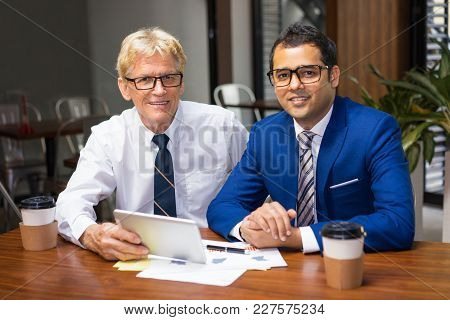 Two Happy Businessmen Using Tablet At Desk With Analytic Documents And Coffee Cups. Two Coworkers Ha