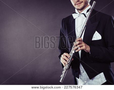 Classical Music, Passion And Hobby Concept. Elegantly Dressed Musician Man Holding Flute. Studio Sho