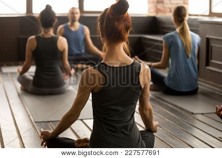 Group Of Young Sporty People Practicing Yoga Lesson With Instructor, Sitting In Sukhasana Exercise,
