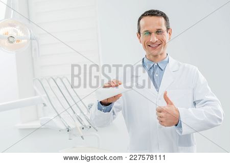 Dentist Showing Blank Toothpaste Tube And Thumb Up In Modern Dental Clinic