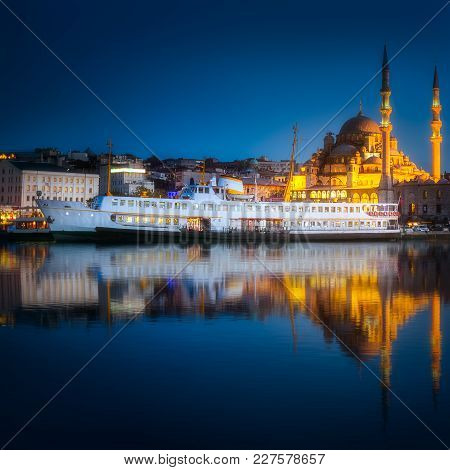 View Of Pier, Public Ferry And Old District Of Istanbul With Mosque On Skyline And Reflection On Wat