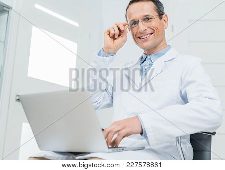 Smiling Doctor Working By Laptop In Modern  Clinic