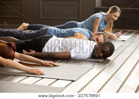 Tired Diverse African And Caucasian People Relaxing Smiling Having Fun Lying On Mat Floor At Yoga Cl