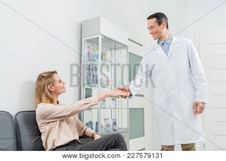 Smiling Doctor Greeting Female Patient Shaking Hands In Modern Dental Clinic