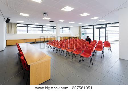 Lonely man in the conference room with red chairs