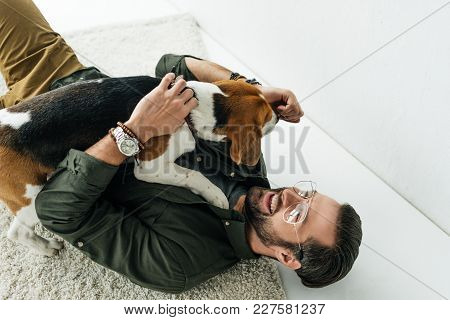 High Angle View Of Smiling Man Lying On Carpet And Playing With Dog