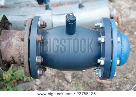 Hot Steam Heating System Pipelines. Ball Valves With Blind Flanges.  City Buldings In The Background