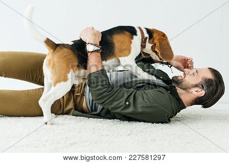Happy Handsome Man Lying On Carpet And Playing With Cute Beagle