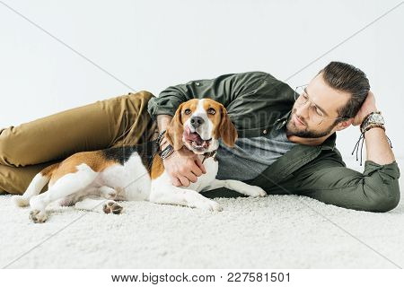 Handsome Man Lying On Carpet With Cute Beagle Isolated On White