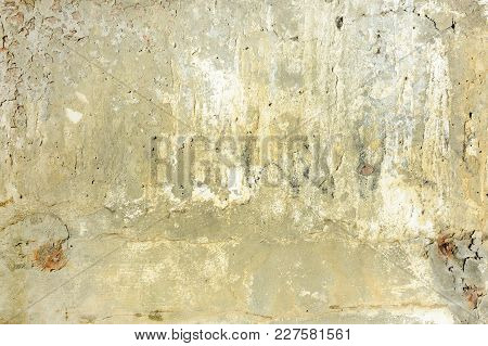 Yellow Concrete Wall With Cracks And Spots. Background With An Unusual Texture.