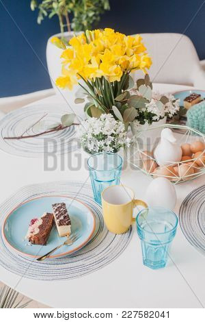 Pastel Table Setting With Yellow Cups, Daffodils And Eggs