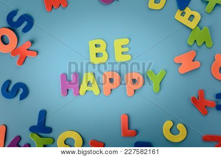 Beautifully Laid Out Inscription Be Happyof Multi-colored Letters. Blue Background With Vignette.