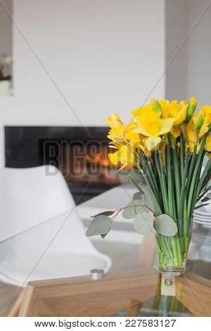Spring Bouquet With Daffodils And Eucalyptus In Glass Vase On Glass Table Top