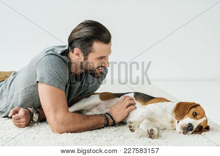 Smiling Handsome Man Lying With Cute Beagle On Carpet