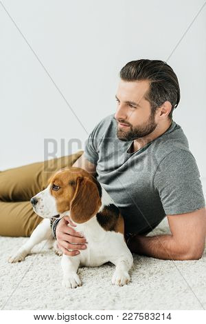 Handsome Man Lying With Cute Beagle On Carpet And Looking Away
