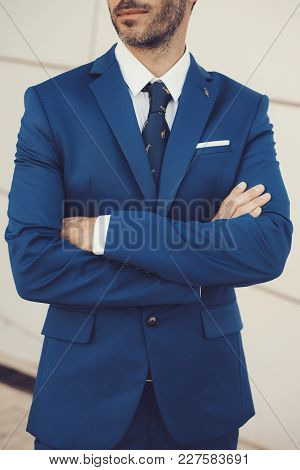 Close-up Portrait Of Elegant Male Model Wearing A Suit With Arms Crossed.