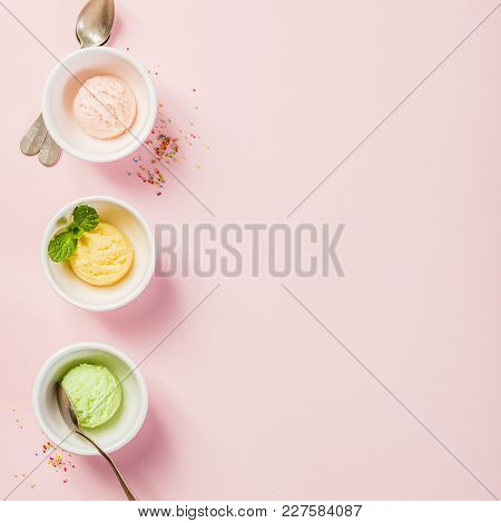 Top view of ice cream in white bowls on pink shabby chic vintage background. Pink (strawberry), yellow (mango or banana) and green (lime, green tea or pistachio).