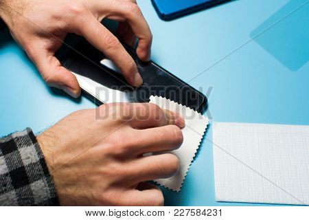 Man Applying Protective Tempered Glass To Phone Screen