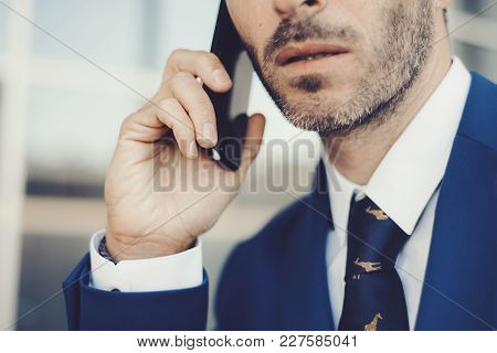 Close-up Portrait Of Elegant Male Model Wearing A Suit Talking On The Phone.