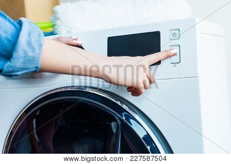 Close-up Partial View Of Woman Using Washing Machine At Home