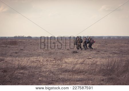 Group Of Men Hunters Gouing Together Through Rural Field In Forward Direction During Hunting Season.