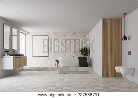 Tiled And White Bathroom Interior With A Tiled Floor, A White Tub, Two Toilets, And A Double Sink. A