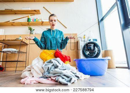 View Of Shocked Young Woman Looking At Laundry