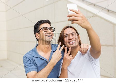 Closeup Portrait Of Two Smiling Handsome Young Men Posing, Showing Victory Signs And Taking Selfie P
