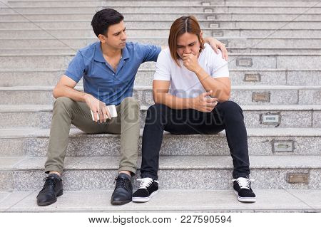 Portrait Of Serious Handsome Young Man Supporting His Depressed Friend And Holding Hand On His Shoul