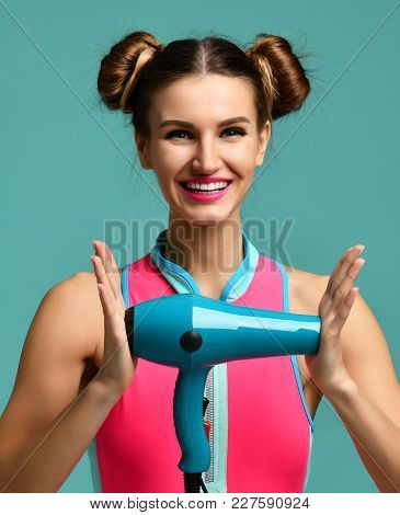 Happy Young Brunette Woman Hold Green Hair Dryer Smiling On Blue Mint Background. Hair Style Beauty
